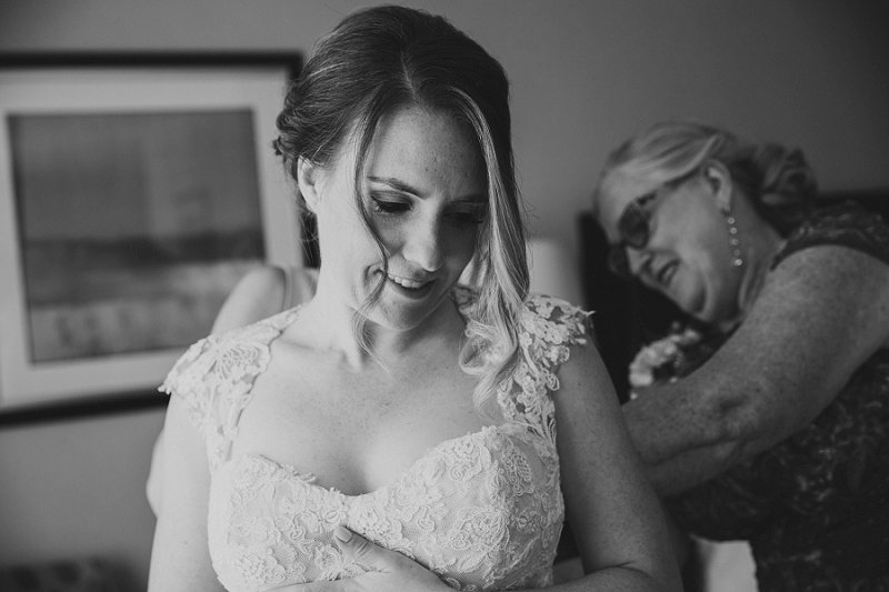 bride getting into dress with mom